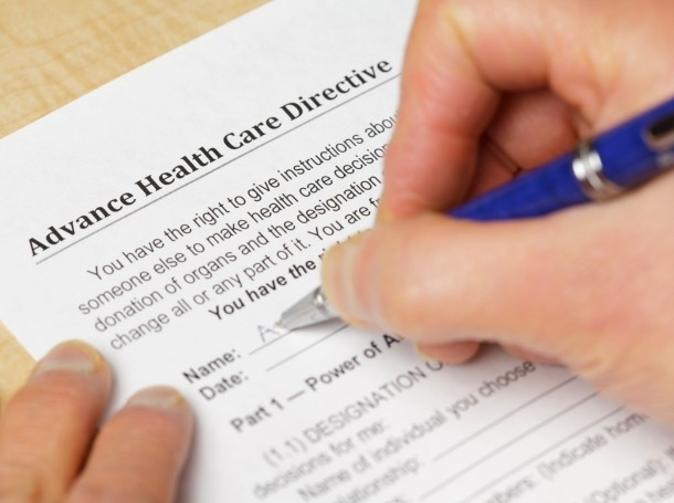 A person filling out a form titled Advance Health Care Directive and a pen, photo by PictureLake/Getty Images