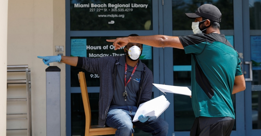 A man speaks with a library worker after receiving an unemployment form in Miami Beach, Florida, April 8, 2020, photo by Marco Bello/Reuters