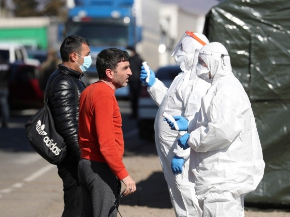 Officials wearing protective gear take body temperatures at a check point, in Marneuli near Tbilisi, Georgia, March 23, 2020, photo by Irakli Gedenidze/Reuters