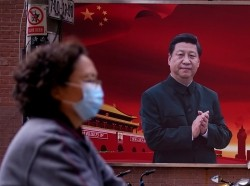 A woman walks past a portrait of Chinese President Xi Jinping, Shanghai, China March 12, 2020, photo by Aly Song/Reuters
