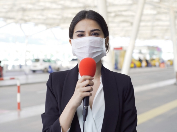 A TV reporter wearing a mask, photo by brightstars/Getty Images