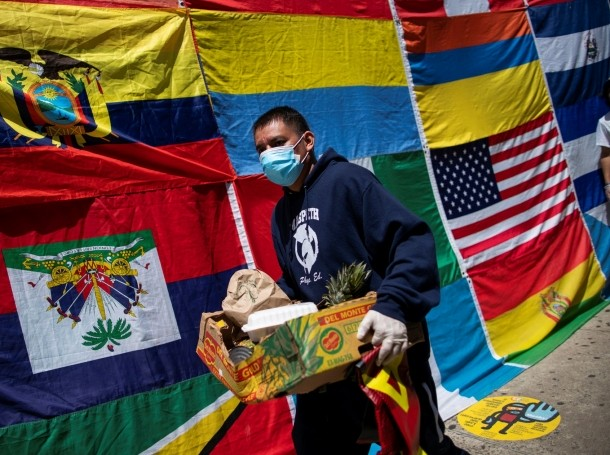 A man carries food donated by Alianza Ecuatoriana International at a food pantry in Queens, New York, May 16, 2020, photo by Eduardo Munoz/Reuters