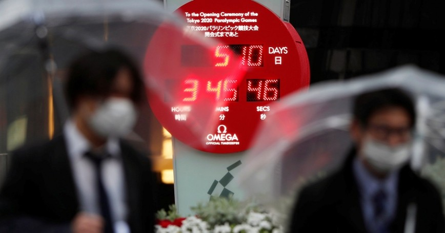 Passersby walk past a countdown clock showing the adjusted days and time until the start of the postponed Tokyo Paralympic Games in Tokyo, Japan, April 1, 2020, photo by Issei Kato/Reuters