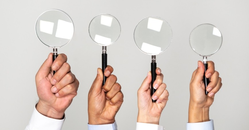 Four hands holding magnifying glasses, photo by solidcolours/Getty Images