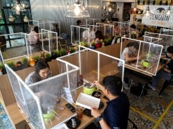 People have lunch at a restaurant that reopened with plastic barriers and social distancing measures to prevent the spread of COVID-19 in Bangkok, Thailand, May 8, 2020, photo by Athit Perawongmetha/Reuters