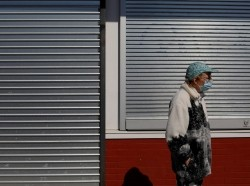 A woman waits in front of a closed and shuttered storefront amid the COVID-19 outbreak in Lynn, Massachusetts, May 4, 2020, photo by Brian Snyder/Reuters