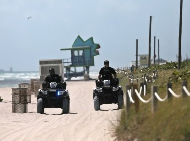 Police officers patrol the beach after the closing of all the beaches in Miami-Dade County due to COVID-19, in Miami Beach, Florida, March 19, 2020, photo by Carlos Barria/Reuters