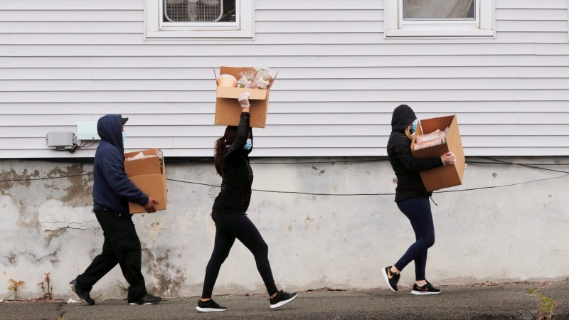 Residents carry boxes of free groceries distributed at a pop-up food pantry by the Massachusetts Army National Guard in Chelsea, Massachusetts, April 24, 2020, photo by Brian Snyder/Reuters