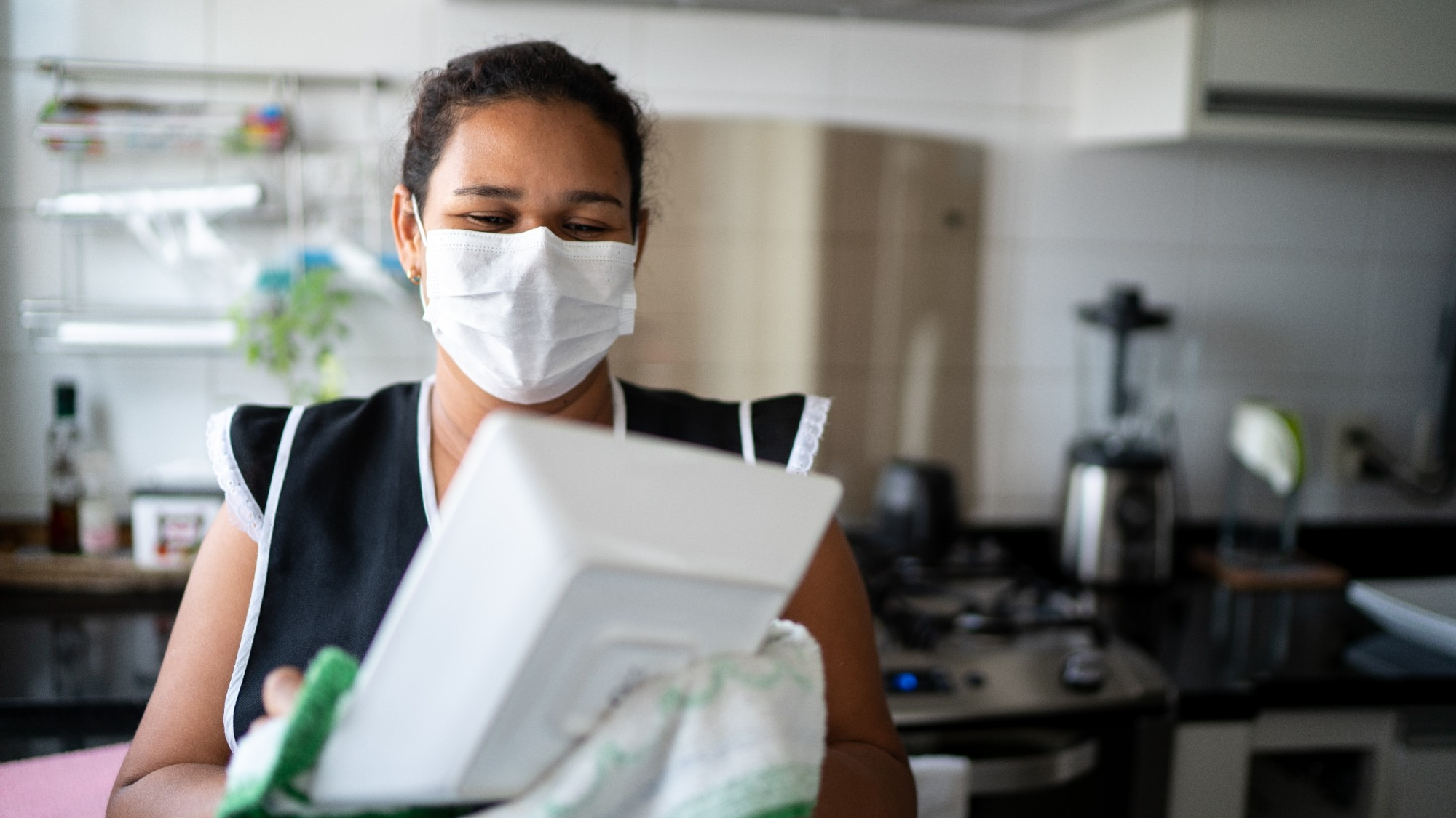 Housekeeper washing the dishes wearing a mask, photo by FG Trade/Getty Images