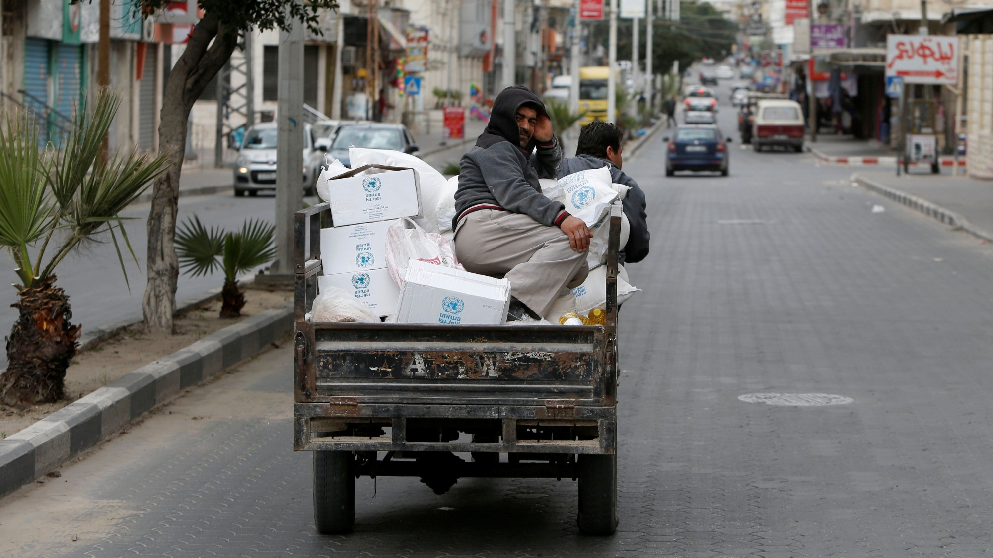A worker rides on a vehicle transporting food supplies distributed by United Nations Relief and Works Agency to the homes of Palestinian refugees as a precaution against the spread of COVID-19, in Gaza City, March 31, 2020, photo by Mohammed Salem/Reuters