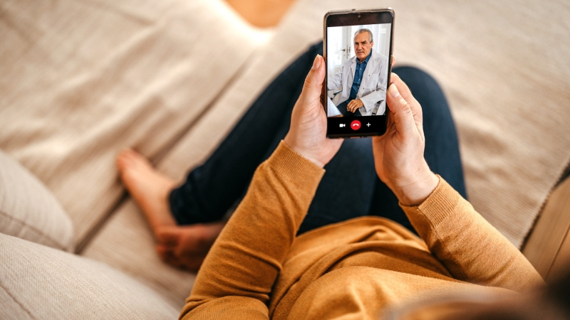 Woman having online consultation with doctor on a smartphone, photo by mixetto/Getty Images