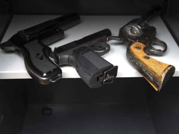 Three guns in an open safe, photo by SERGEI PRIMAKOV/Adobe Stock