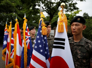 South Korean soldiers hold flags of countries that fought in the Korean War at a ceremony commemorating the 70th anniversary of the war, near the demilitarized zone separating the two Koreas, in Cheorwon, South Korea, June 25, 2020, photo by Kim Hong-Ji/Reuters