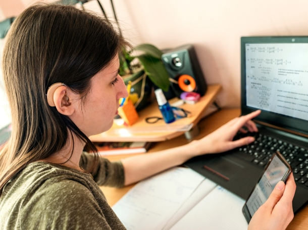 Teenage girl with hearing aid having online school class at home, photo by Sladic/Getty Images