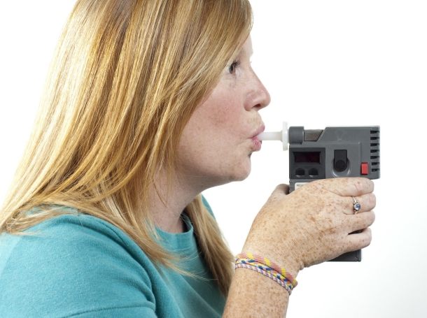 A woman blowing into a breath monitor, photo by aijohn784/Getty Images