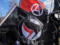 Members of the Great Lakes anti-fascist organization (Antifa) fly flags during a protest against the Alt-right outside a hotel in Warren, Michigan, March 4, 2018, photo by Stephanie Keith/Reuters