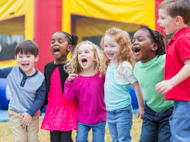 A group of six multi-ethic children, 3-4 years old, standing in the park together, laughing and shouting, photo by kali9/Getty Images