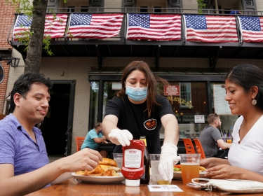 As phase one of reopening begins in Northern Virginia, a waitress with a face mask serves diners at a restaurant in Alexandria, Virginia, May 29, 2020, photo by Kevin Lamarque/Reuters