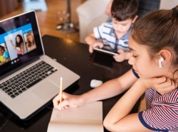 Teenage girl studying with video online lesson at home, photo by valentinrussanov/Getty Images