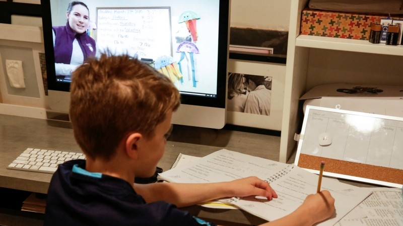 Oakes McClenahan, 7, watches his teacher's recorded lesson on a computer at home, Seattle, Washington, March 27, 2020, photo by Jason Redmond/Reuters