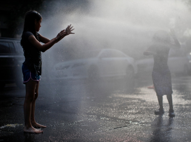Children cool off under the spray from an open fire hydrant in the Washington Heights section of upper Manhattan in New York City, July 17, 2013, photo by Mike Segar/Reuters
