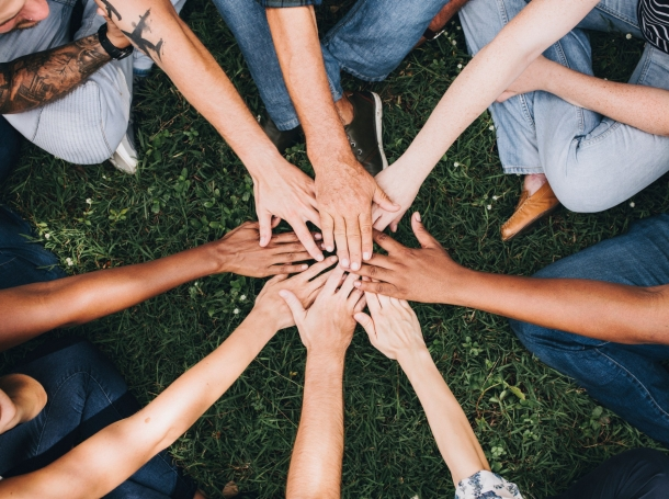 People stacking hands together in the park, photo by Rawpixel/Getty Images