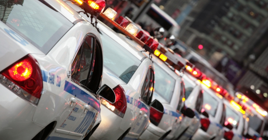 A long line of police squad cars, photo by thall/Getty Images