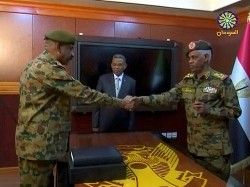 Sudan's Defence Minister Awad Mohamed Ahmed Ibn Auf, head of Military Transitional Council, and the military's chief of staff Lieutenant General Kamal Abdul Murof Al-mahi shake hands after being sworn in as leaders of Military Transitional Council in Sudan in this still image taken from video on April 11, 2019, photo by Sudan TV/Reuters