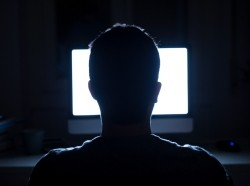 A man seated in front of a computer monitor in a dark room, photo by tommaso79/Getty Images