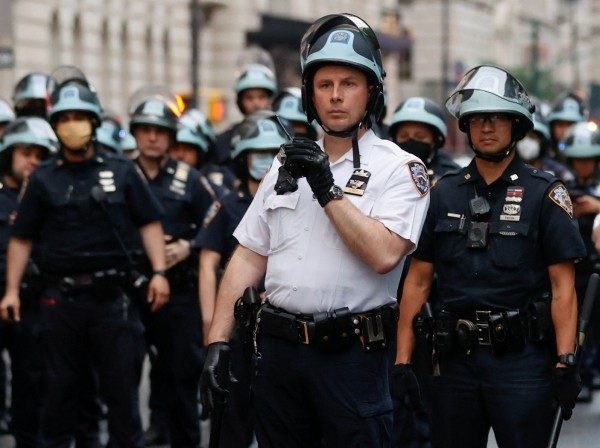 Police officers stand guard across Central Park West during a protest against the death in Minneapolis police custody of George Floyd, in New York City, June 5, 2020, photo by Mike Segar/Reuters