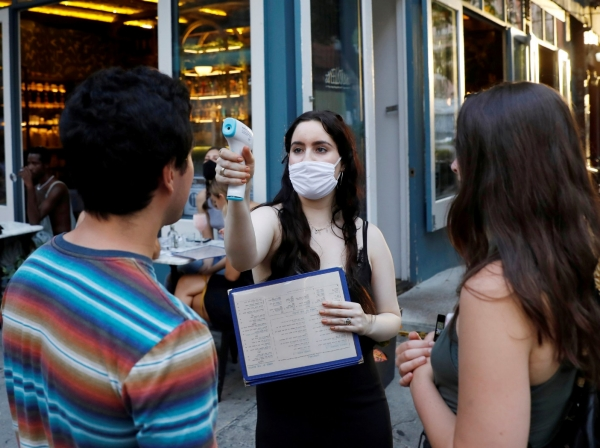 A waitress takes the temperature of customers as restaurants are permitted to offer al fresco dining as part of phase 2 reopening in New York City, June 27, 2020, photo by Andrew Kelly/Reuters