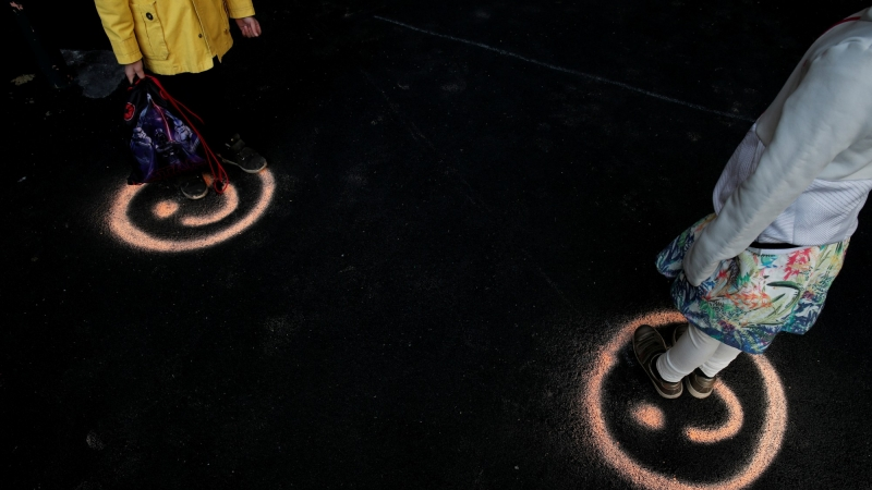 Children stand on smiley faces to maintain social distancing in the courtyard of a school in Paris, France, May 14, 2020, photo by Benoit Tessier/Reuters