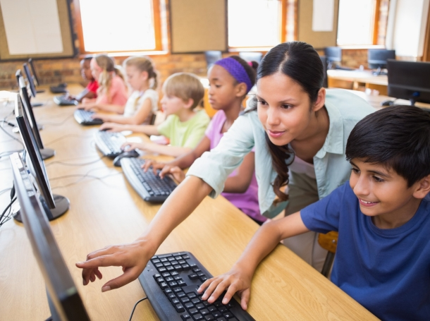 Students using laptops in class, with a teacher assisting one student, photo by Wavebreakmedia/Getty Images