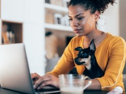 Young Black woman working on a computer at home with her dog on her lap, photo by filadendron/Getty Images