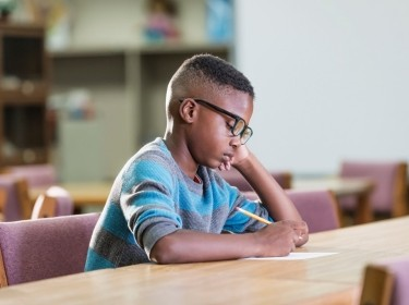 A young Black boy writing at a table, photo by kali9/Getty Images
