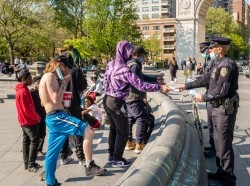 NYPD officers distribute face masks in Washington Square Park, New York City, May 10, 2020, photo by nycshooter/Getty Images