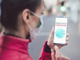 Woman using a phone with a coronavirus tracking app installed, photo by kzenon/Getty Images