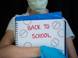 Child wearing a face mask and gloves, holding a binder with Back to School and drawings of coronavirus, photo by Amy Mitchell/Getty Images