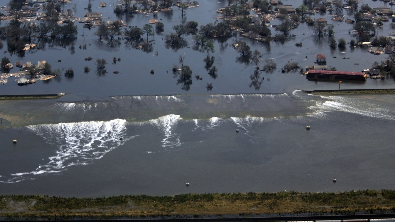 A levee gives way to high water in New Orleans, Louisiana, after Hurricane Katrina struck on August 31, 2005