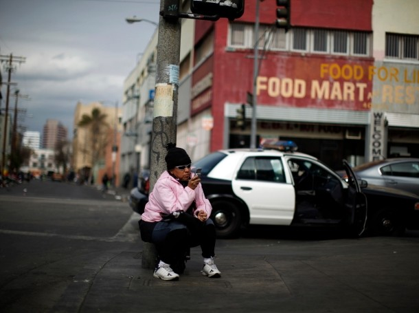 A woman uses a cell phone on downtown Los Angeles' Skid Row, March 6, 2013, photo  by Lucy Nicholson/Reuters