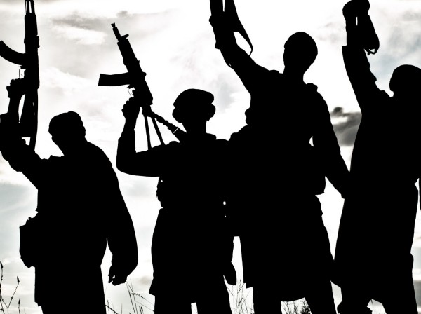 Silhouette of several militants with rifles, photo by zabelin/Getty Images