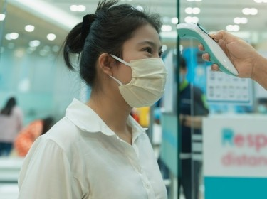 Woman in a face mask having her temperature scanned, photo by whyframestudio/Getty Images