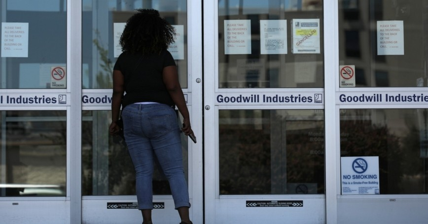 A woman looks for information on the application for unemployment support at the New Orleans Office of Workforce Development in New Orleans, Louisiana, April 13, 2020, photo by Carlos Barria/Reuters