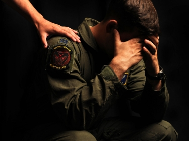 A U.S. Air Force airman sits with his head in his hands, an arm from offscreen reaches to put a hand on his shoulder, photo by Nadine Barclay, TSgt/U.S. Air Force