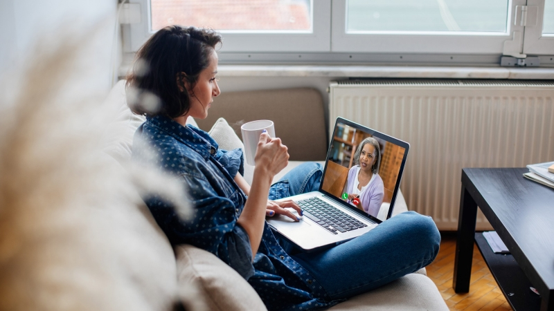 Woman sitting on her couch having a virtual medical appointment on her laptop, photos by Agrobacter and SDI Productions/Getty Images