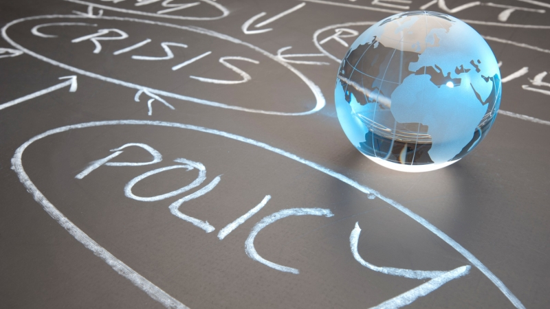 Glass globe sitting on chalk board with crisis and policy written in chalk, photo by courtneyk/Getty Images
