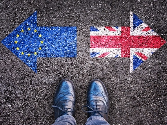 Arrows with UK and EU flag images pointing in opposite directions on the ground, with legs and shoes viewed from above, photo by Delpixart/Getty Images