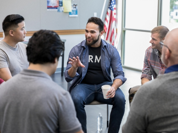Mid adult Hispanic male veteran gestures as he discusses something during a veterans group meeting,  photo by SDI Productions/Getty Images