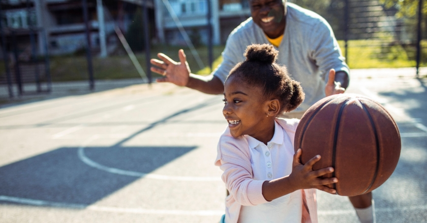 Close up of a grandfather taking his granddaughter to play some basketball in the park, photo by Geber86/Getty Images