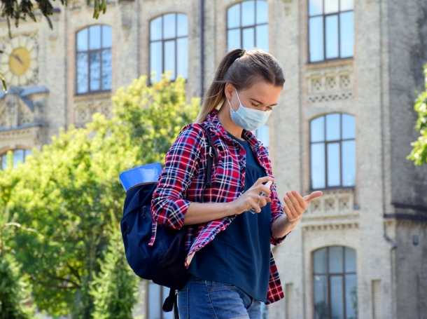College student using hand sanitizer, wearing a face mask, and walking on a college campus, photo by Nemer-T/Getty Images